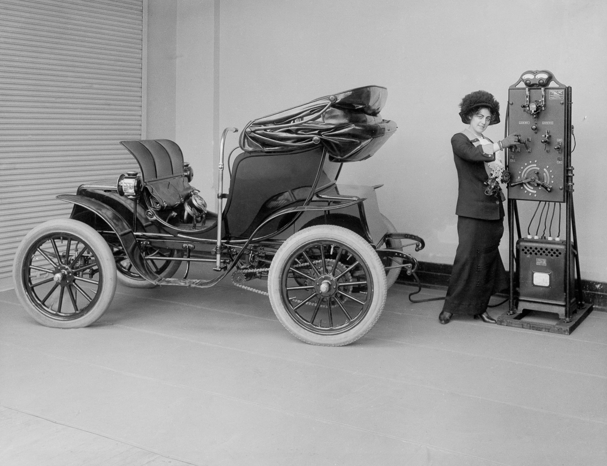 ca. 1912, A young woman uses a hand-cranked battery charger to charge her electric Columbia Mark 68 Victoria automobile.